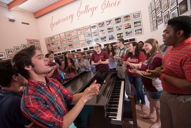 choir students sing around piano