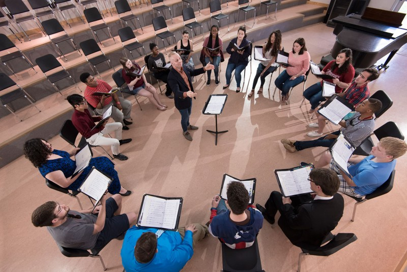 Choir students rehearse in a circle
